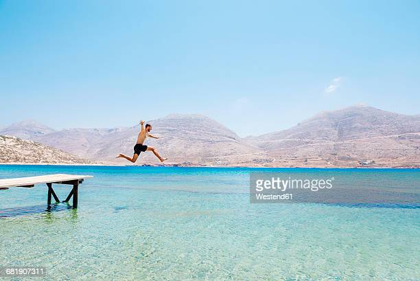 Greece, Cyclades islands, Amorgos, Aegean Sea, naked man jumping from a wooden jetty