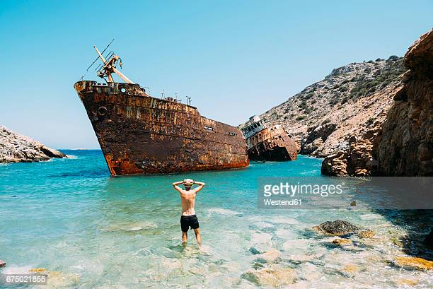 Greece, Cyclades Islands, Amorgos, Man at the beach, visiting a shipwreck, Olympia