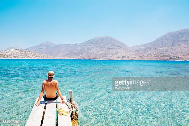 Greece, Cyclades islands, Amorgos, man sitting on the edge of a wooden pier, Nikouria island