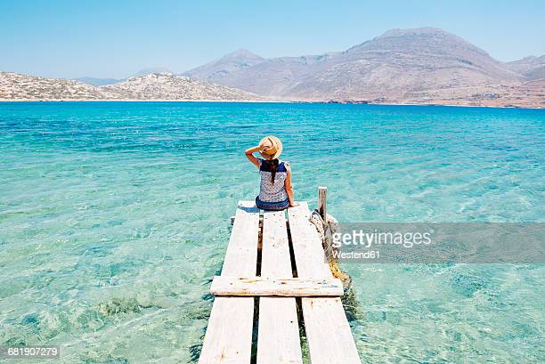 Greece, Cyclades islands, Amorgos, woman sitting on the edge of a wooden pier, Nikouria island