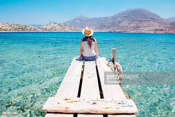 greece, cyclades islands, amorgos, woman sitting on the edge of a wooden pier, nikouria island - jetty stock pictures, royalty-free photos & images