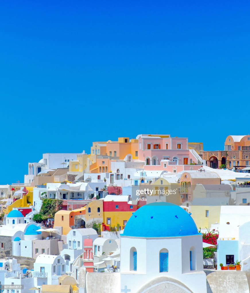 Greece, Cyclades, Santorini Island (also Thera or Thira): churches with blue dome and traditional whitewashed houses with colourful facades in the village of Oia.