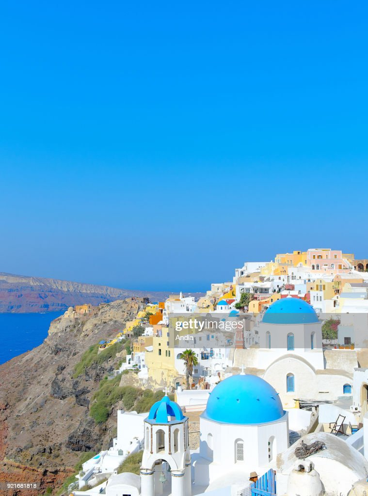 Greece, Cyclades, Santorini Island (also Thera or Thira): churches with blue dome and traditional whitewashed houses in the village of Oia.