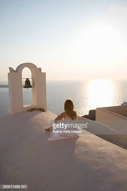 Greece, Cyclades, Santorini, Oia, woman facing sea, rear view, sunset