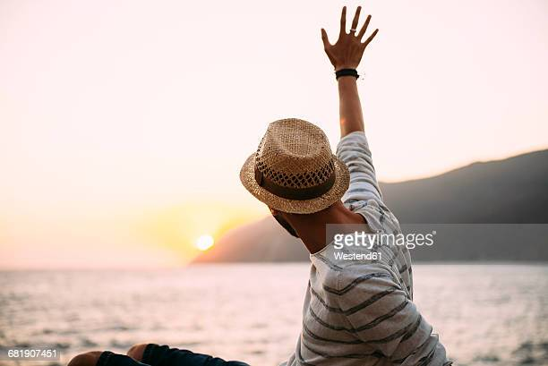 greece, cylcades islands, amorgos, man waving and enjoying the sunset next to the sea - waving gesture stock photos and pictures