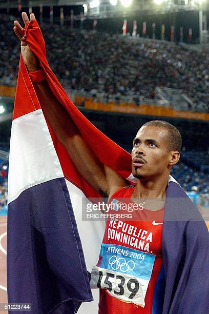 Dominican Republic's Felix Sanchez celebrates with his country's flag after winning the men's 400m hurdles final at the Olympic Stadium 26 August...