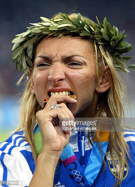 Fani Halkia of Greece bites the gold medal she won in the women's 400m hurdles finals 25 August 2004 during the Olympic Games athletics competitions...