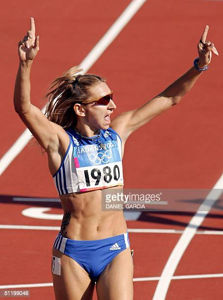 Fani Halkia of Greece gestures after she won heat four round one of the women's 400m hurdles 21 August 2004 during the Olympic Games athletics...