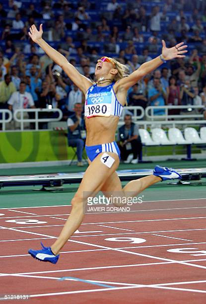 Fani Halkia of Greece throws her hands up as she finishes first in the women's 400m hurdles 25 August 2004 during the Olympic Games athletics...