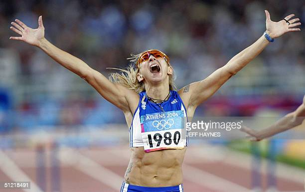 Fani Halkia of Greece throws her hands up in the air after she crosses the finish line first to win gold in the women's 400m hurdles final 25 August...