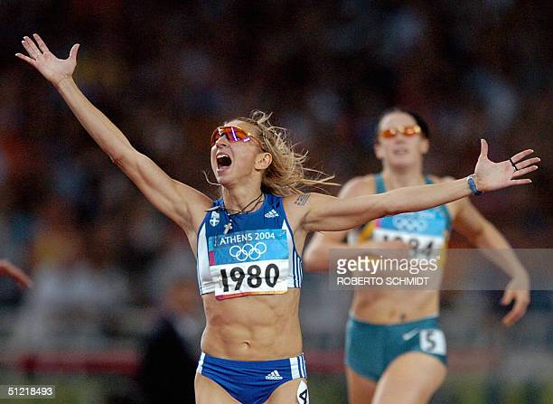 Fani Halkia of Greece throws her hands up in the air after she crosses the finish line first ahead of Australia's Jana Pittman to win gold in the...
