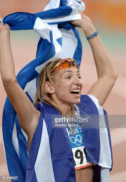 Fani Halkia of Greece waves her national flag on a victory lap after she won gold in the women's 400m hurdles final 25 August 2004 during the Olympic...