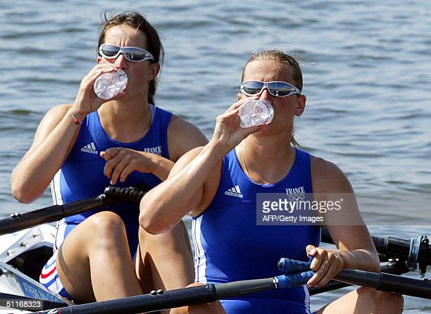France's Caroline Delas and Gaelle Buniet drink water after finishing first during the Women's double sculls Heat 1 at the Schinias rowing and...