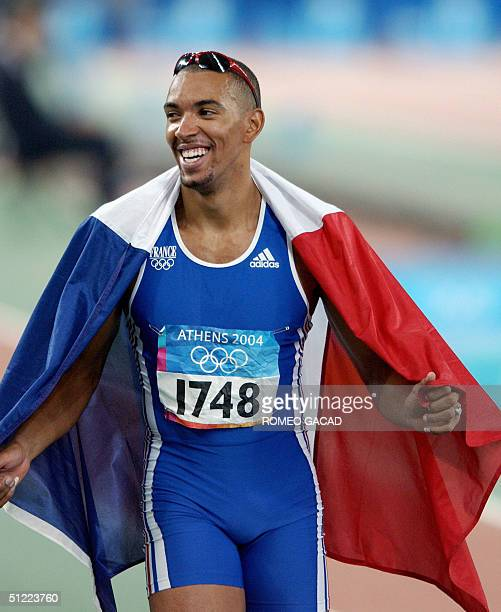 France's Naman Keita celebrates with his country's flag after winning the bronze in the men's 400m hurdles final at the Olympic Stadium 26 August...
