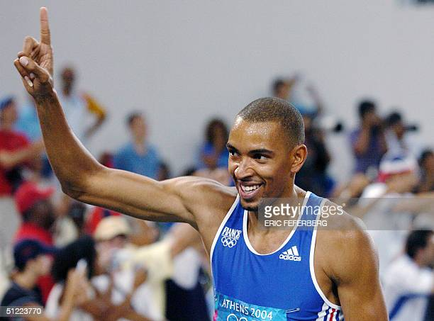 France's Naman Keita celebrates with his country's flag after winning the bronze the men's 400m hurdles final at the Olympic Stadium 26 August 2004...