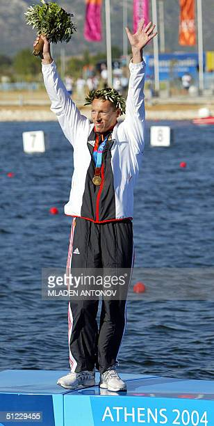German Andreas Dittmer waves to the crowd from the podium during the medal ceremony for the Men's C1 500m final for the Athens 2004 Olympic Games at...