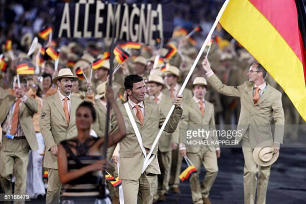 German equstrian champion Ludger Beerbaum carries his country's flag as he leads the German delegation into the Olympic Stadium in Athens during the...