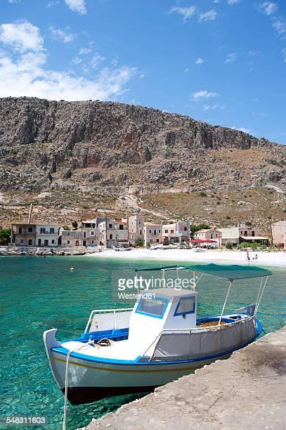 greece, gerolimenas, fishing boat and stone houses - peninsula de grecia fotografías e imágenes de stock