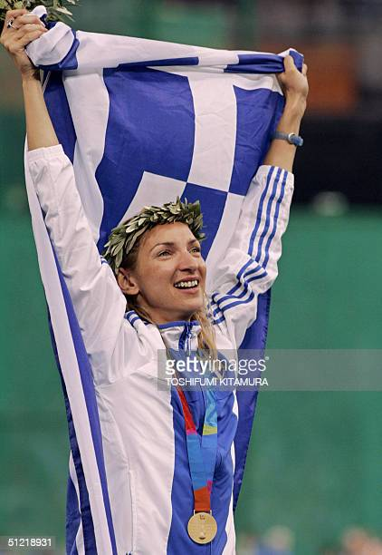 Gold winner Fani Halkia of Greece stands on the winners' podium during the medal ceremony for the women's 400m hurdles finals 25 August 2004 during...