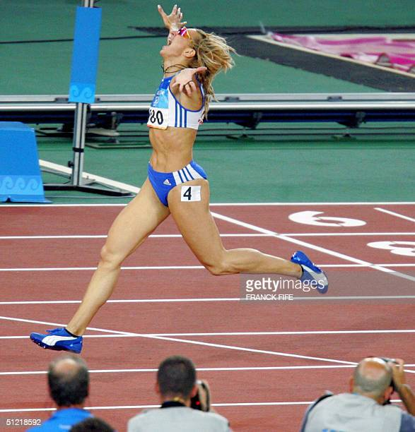 Greece's Fani Halkia celebrates after winning the women's 400m hurdles at the Olympic Stadium 25 August 2004 during the Olympic Games athletics...