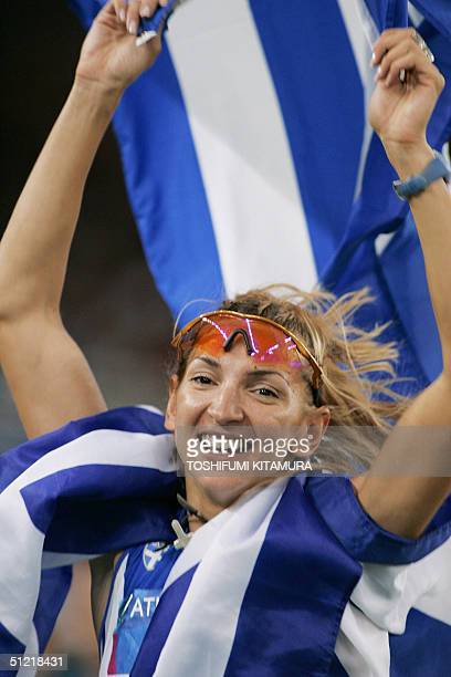 Greece's Fani Halkia celebrates with her country's flag after winning the gold medal in the women's 400m hurdles at the Olympic Stadium 25 August...