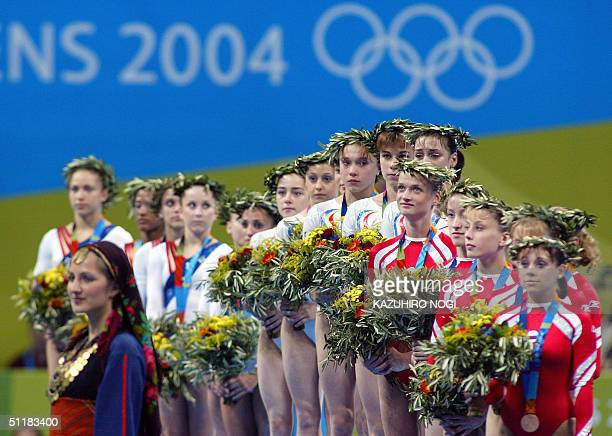 Gymnasts of Romania pose on the podium 17 August 2004 at the Olympic Indoor Hall after winning the gold medal of the women's artistic gymnastics team...