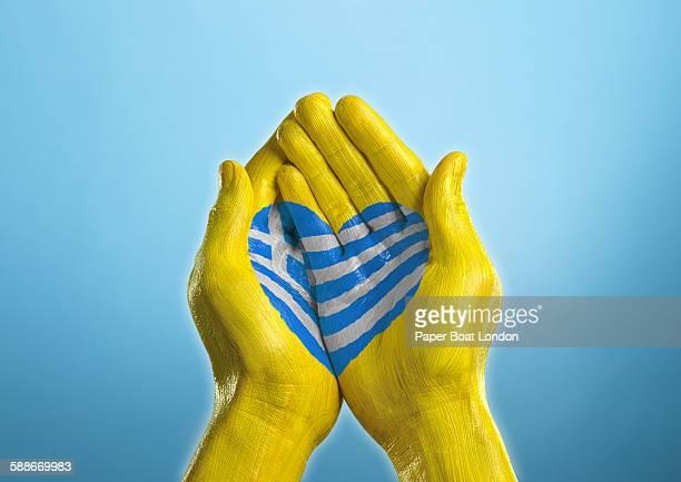 greece heart shaped flag painted on a hand