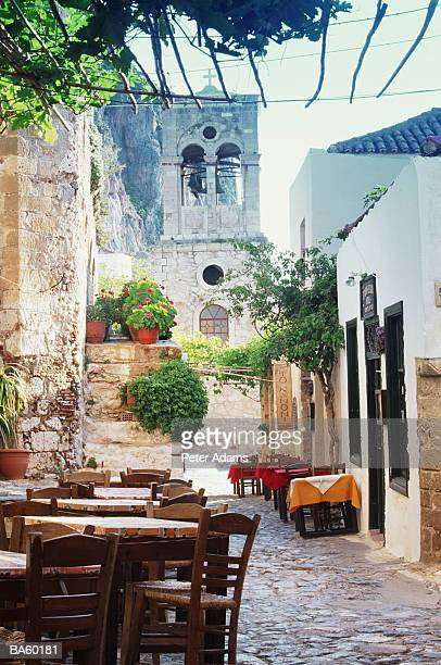 greece, hydra, tables outside restaurant - hydra greece stock photos and pictures