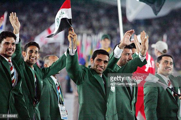 Iraqi athlete Hadir Lazame holds up his country's flag as he leads the Iraqi delegation into the Olympic Stadium in Athens during the opening...