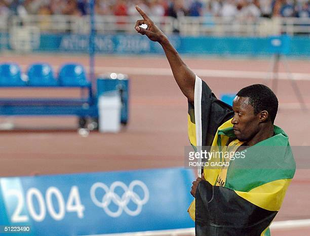 Jamaica's Danny McFarlane celebrates with his country's flag after winning the silver the men 400m hurdles final at the Olympic Stadium 26 August...
