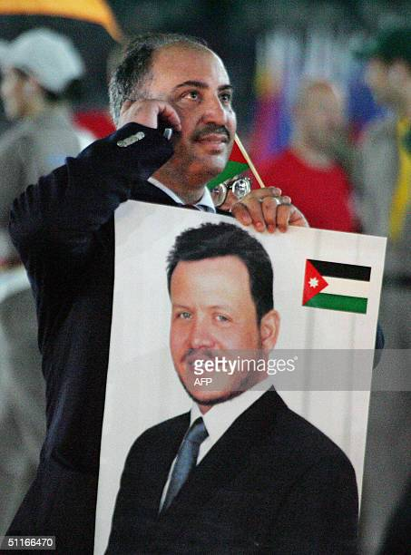 Jordanian Khalil Al-Hanahnahe holds a picture of Jordanian King Abdulah II as he leads the Jordanian delegation into the Olympic Stadium in Athens...