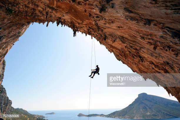 Greece, Kalymnos, climber abseiling in grotto