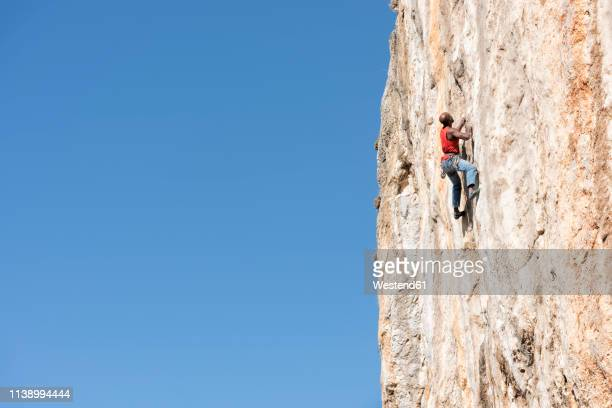 greece, kalymnos, climber in rock wall - rock wall stock pictures, royalty-free photos & images