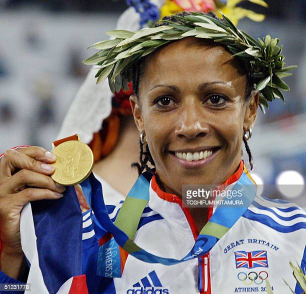 Kelly Holmes of Great Britain holds up the gold medal she won in the women's 1500m final 28 August 2004 during the Olympic Games athletics...