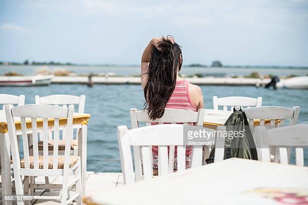 Greece, Lefkada, woman sitting in a Greek taverna by the sea