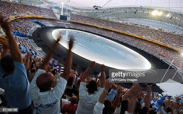 """Members of the audience perform """"the wave"""" as they wait in the Athens Olympic Stadium for the start of 2004 summer games opening ceremony, 13 August..."""