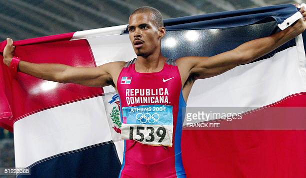 Men's 400m hurdles gold winner Felix Sanchez of the Dominican Republic holds up his national flag after the final 26 August 2004 during the Olympic...