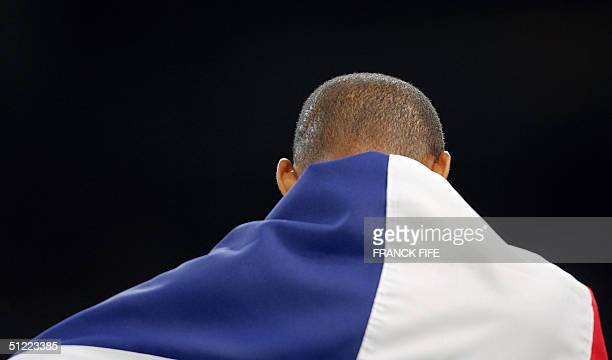 Men's 400m hurdles gold winner Felix Sanchez of the Dominican Republic drapes his national flag around his shoulders after the final 26 August 2004...