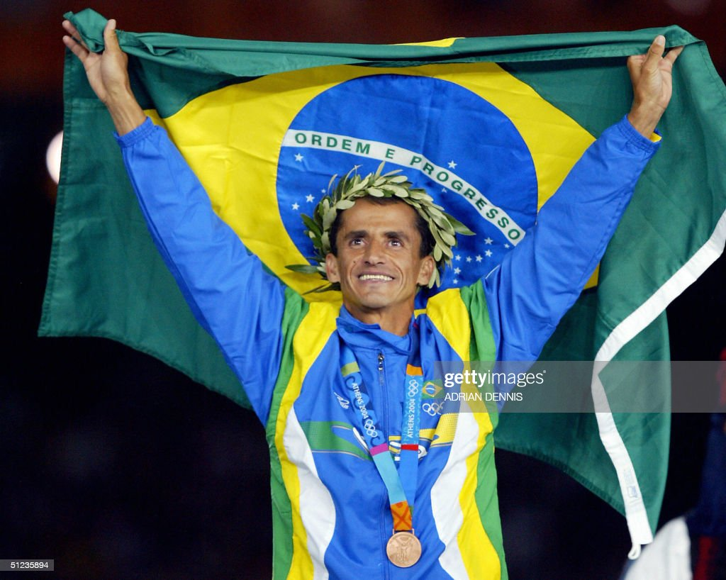 Men's marathon bronze medal winner Vanderlei de Lima of Brazil stands on the winners' podium 29 August 2004, during the Olympic Games medals ceremony at the Olympic Stadium in Athens. Long-time race leader de Lima was attacked by a spectator in the latter stages of the race but recovered and hung on to win the bronze while Stefano Baldini of Italy won the gold and Mebrahtom Keflezighi of the US took the silver.