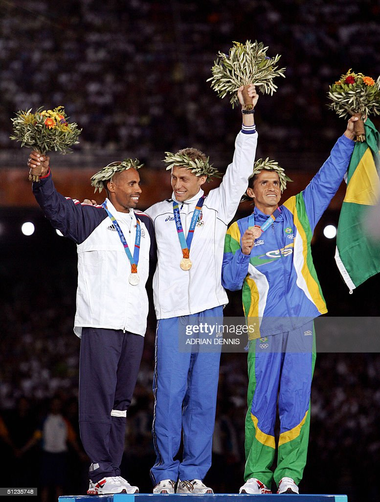 Men's marathon gold medal winner Stefano Baldini of Italy, silver winner Mebrahtom Keflezighi of the US and bronze winner Vanderlei de Lima of Brazil stand on the winners' podium, 29 August 2004, during the Olympic Games medal ceremony at the Olympic Stadium in Athens. Long-time race leader de Lima was attacked by a spectator in the latter stages of the race but recovered and hung on to win the bronze.