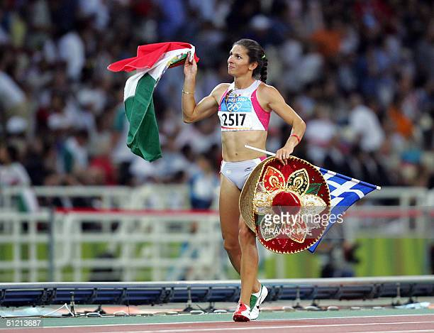 Mexico's Ana Guevara celebrates with her country's flag while running a lap of honour after she won the silver in the women's 400m final at the...