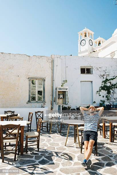 Greece, Milos, Klima, Man sitting in empty cafe, relaxing