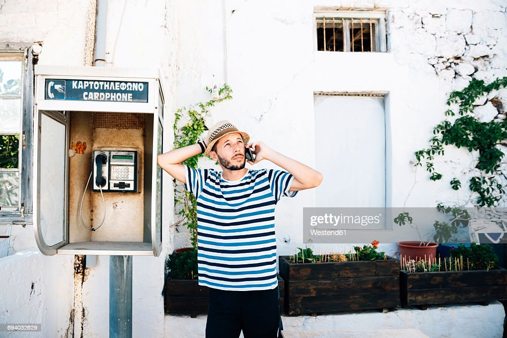 Greece, Milos, Klima, Man talking on cell phone, leaning against old telephone booth : Photo