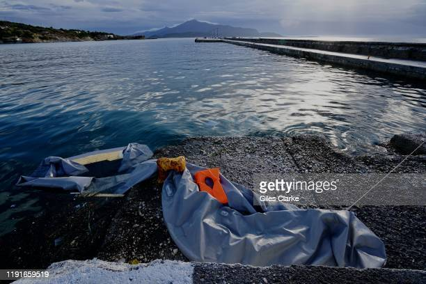 SAMOS Greece November 28 2019 A halfsunken inflatable boat lies abandoned in the port of Pythagorio in Samos Greece In the distance the outline of...