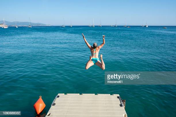 greece, parga, carefree woman jumping from jetty into the sea - epirus greece stock pictures, royalty-free photos & images