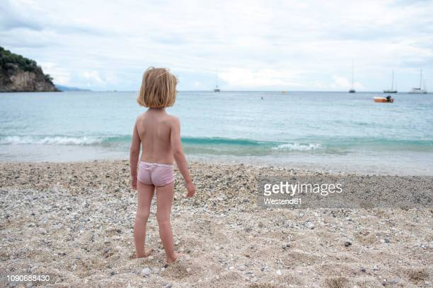 greece, parga, little girl standing on the beach - epirus greece stock pictures, royalty-free photos & images