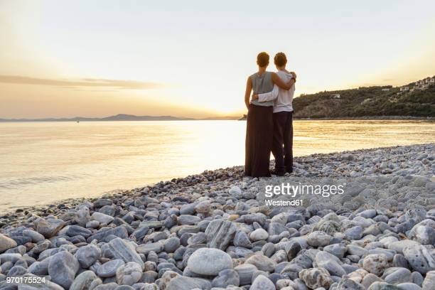 Greece, Pelion, couple enjoying at sunset at beach