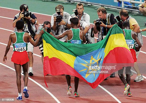 Photographers take pictures of reigning world 10,000m world champion and record holder Kenenisa Bekele of Ethiopia after he won the gold in the men's...