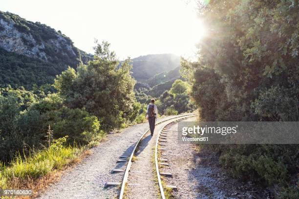 greece, pilion, milies, back view of man walking along rails of narrow gauge railway - pelion stock pictures, royalty-free photos & images
