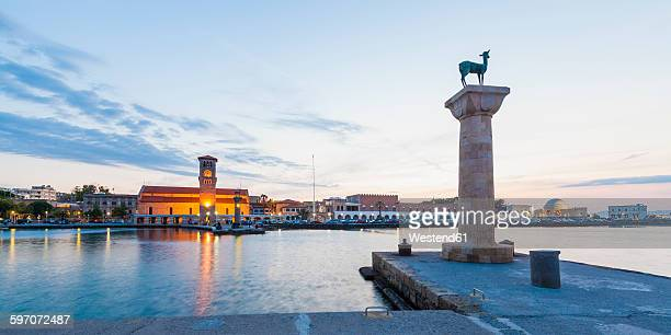 Greece, Rhodes, entrance to Mandraki harbour at dusk